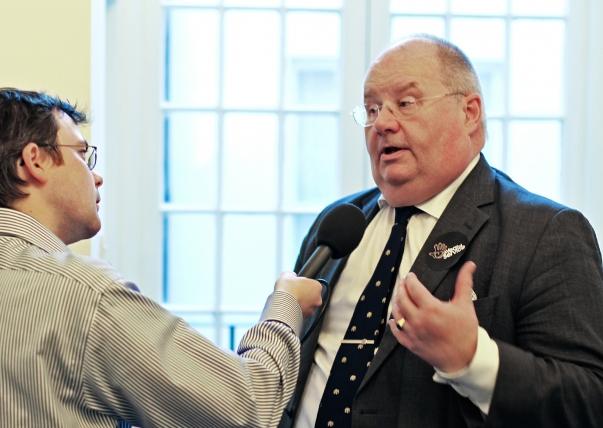 """Az Egyesült Királyság közösségekért és helyi önkormányzatokért felelős államtitkára, Eric Pickles parlamenti képviselő egy rádióriporter kérdéseire válaszol az """"Éves Szolgálat"""" programmal kapcsolatban, amely egy olyan – kormány által támogatott – kezdeményezés, melynek célja az önkéntes szolgálatra ösztönzés az Egyesült Királyság kilenc fő vallási közössége révén. A program elindítására és első önkéntes napjára 2012. február 28-án került sor a londoni Országos Bahá'í Központban. © Bahá'í Nemzetközi Hírszolgálat news.bahai.org"""