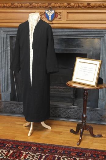 """Az 'Abdu'l-Bahá által viselt köntös, valamint a londoni City Temple-ben 1911. szeptember 10-én tartott legelső nyilvános beszéd egy bekeretezett mondata: """"Isten ajándéka ezen megvilágosodott kor számára az emberiség egységének és a vallás alapvető egységének a tudása."""" A történelmi jelentőségű tárgyakat az Őfelsége II: Erzsébet uralkodásának gyémánt jubileumát köszöntő fogadáson mutatták be a Lambeth palotában. © Bahá'í Nemzetközi Hírszolgálat news.bahai.org"""