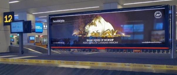 """Az Újdelhi nemzetközi repülőtérre érkező utasok csomagjaikra várva, a bahá'í imaház látképével, """"a közösségi harmónia indiai jelképével"""" találkoznak. © Bahá'í Nemzetközi Hírszolgálat news.bahai.org"""