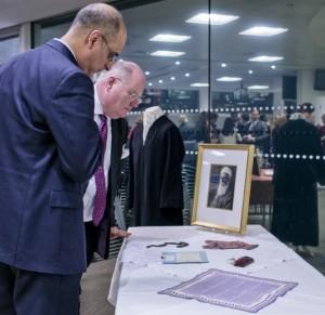 Eric Pickles a Közösségek és Helyi Önkormányzatok Minisztériumának államtitkára, parlamenti képviselő (jobbra) 'Abdu'l-Bahá személyes és történelmi tárgyait tekinti meg a brit kormány által a bahá'í közösség tiszteletére adott fogadáson 2012. november 28-án. © Bahá'í Nemzetközi Hírszolgálat news.bahai.org