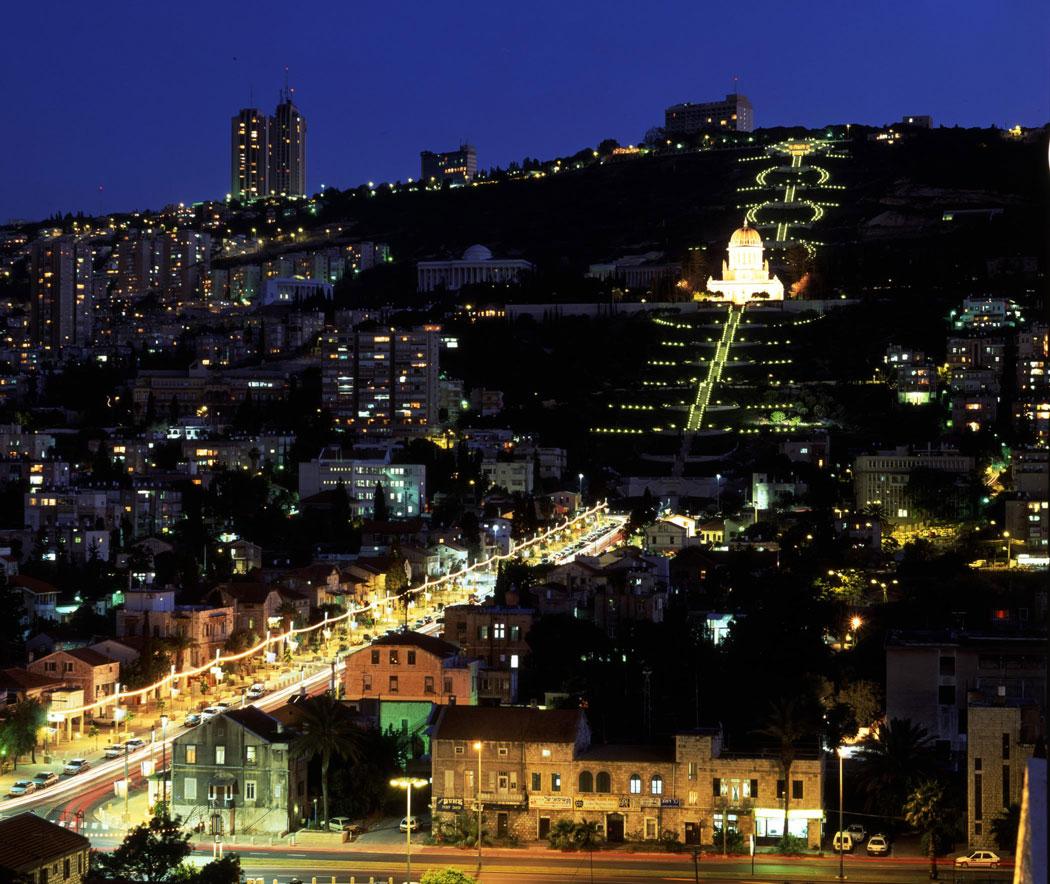 Haifa esti kivilágításban: a hegy lábánál a Német Templomosok piros cserepes házai, fentebb a bahá'í kert © Bahá'í Nemzetközi Közösség media.bahai.org