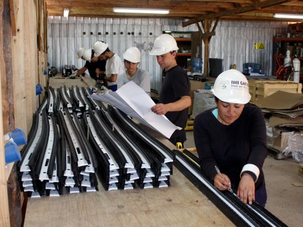 Nemzetközi önkéntesek a templom felépítménye elemeinek előkészítésében © Bahá'í Nemzetközi Hírszolgálat news.bahai.org