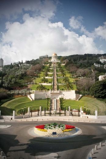 Az UNESCO Tolerancia és Béke tere egy művész látványtervén. Háttérben a bahá'í kert, melyet 2008-ban vettek fel az UNESCO Világörökség listájára. A fejlesztési tervek között szerepel a kövezet felújítása, valamint a körforgalom közepének virágosítása, szimbolikus hidat képezve a német templomosok kolóniája és a bahá'í kertek között. (Haifa, Izrael) © Bahá'í Nemzetközi Hírszolgálat news.bahai.org