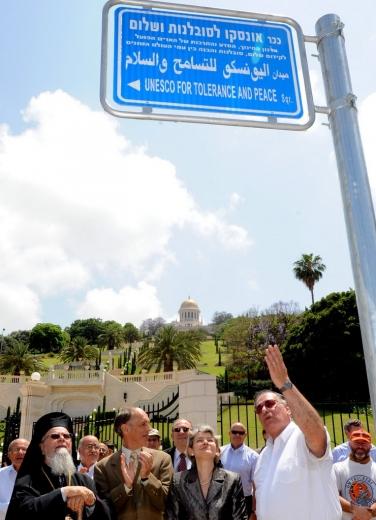 Az UNESCO Tolerancia és Béke terét jelző héber, arab és angol nyelvű tábla, amelyet 2011. május 29-én lepleztek le az izraeli Haifában. A jelenlévők (első sor, balról jobbra): főtiszteletű Dr. Elias Chacour, a Melkita-Görög Katolikus Egyház Akkó, Haifa, Názáret és Egész Galilea főérseke; Dr. Albert Lincoln, a Bahá'í Nemzetközi Közösség főtitkára; Irina Bokova, az UNESCO főigazgatója; valamint Yona Yahav, Haifa polgármestere. © Bahá'í Nemzetközi Hírszolgálat news.bahai.org